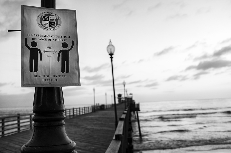 Image of City of Oceanside physical distancing signage, pier, and ocean